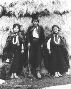 Due foto storiche di Mapuche davanti alla ruca (capanna) tradizionale. Una famiglia e, sotto, una tessitrice al lavoro sul telaio tradizionale